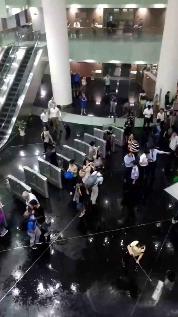 Người dân che dù, tránh dột trong tòa nhà Bitexco