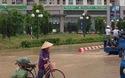 Một người dân thụt xuống hố ga ở đoạn đường ngập bên ngoài khu nhà HH2 Dương Nội.
